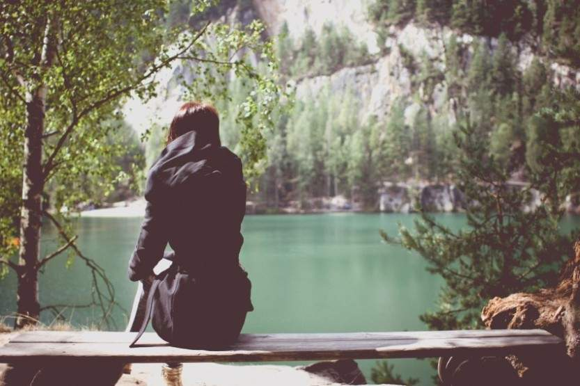 girl sitting alone lonely water rock