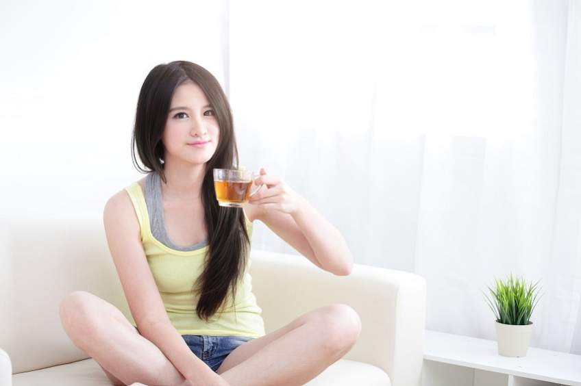 Beautiful happy young woman sitting with hot tea
