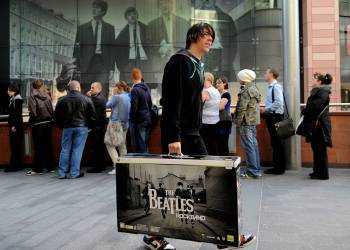 """Beatles fans queue outside the HMV music store in Liverpool, north west England during the rush to purchase the new Beatles Rock Band interactive computer game and digitally remastered albums, on September 9, 2009. A new wave of Beatlemania swept around the world Wednesday as the Fab Four's digitally remastered albums and a new computer game were released. Fans queued up from Tokyo to London to get their hands on the rejuvenated and cleaned-up versions of all the legendary British quartet's entire back catalogue, and the """"The Beatles: Rock Band"""" game. AFP PHOTO/PAUL ELLIS / AFP / PAUL ELLIS"""