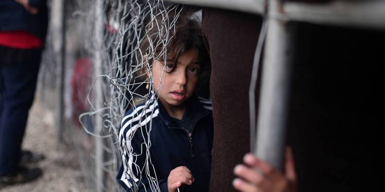 A child waits to get some breakfast in the makeshift camp at the Greek-Macedonian border near the village of Idomeni where thousands of migrants and refugees are stranded on March 7, 2016.  European Union leaders will on March 7 back closing down the Balkans route used by most migrants to reach Europe, diplomats said, after at least 25 more people drowned trying to cross the Aegean Sea en route to Greece. The declaration drafted by EU ambassadors on March 6 will be announced at a summit in Brussels on March 7, set to also be attended by Turkish Prime Minister Ahmet Davutoglu.   / AFP / LOUISA GOULIAMAKI