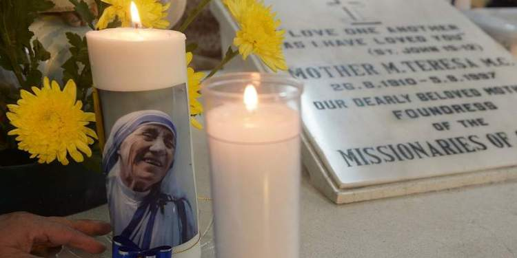 A nun of ?the Missionaries of Charity lights candles on Mother Teresa's tomb prior to a special prayer service at Mother House in Kolkata on December 18, 2015.   Mother Teresa, set to become a saint after the Vatican announced recognition of her second miracle, became a global symbol of compassion for her care of the sick and destitute.  AFP PHOTO/ DIBYANGSHU SARKAR / AFP / DIBYANGSHU SARKAR
