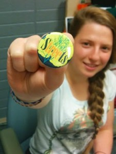 A young woman holds a lapel button toward the camera. The button text says