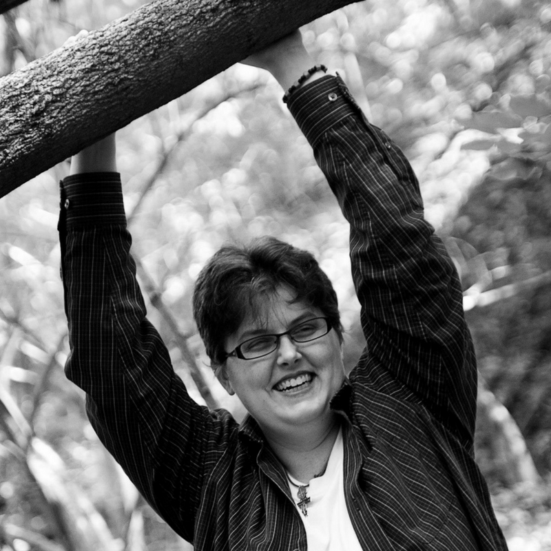 A picture of me outside with my hands resting on a tree branch over my head