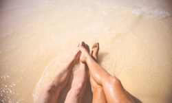Couple with feet in ocean.