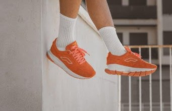 https://www.pexels.com/photo/person-in-red-nike-sneakers-sitting-on-concrete-wall-9400761/