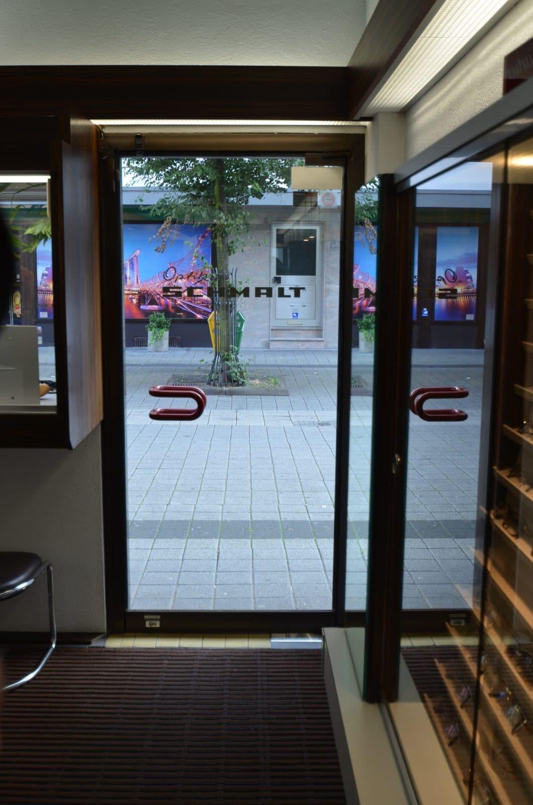 """Foto der linken Ladentür mit Logo """"Optiker Schmalt"""""""