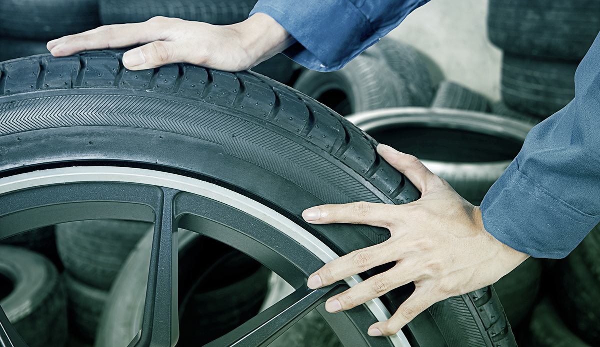 hight resolution of garage worker with a wheel at orange tyres uttoxeter