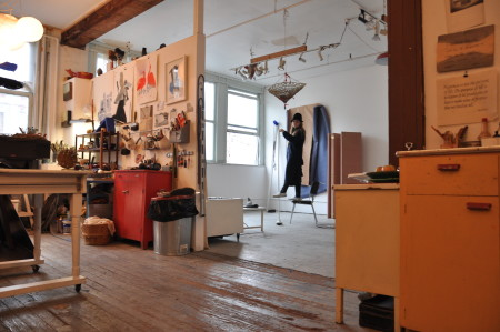 Standing at the far room in her studio, in a long overcoat and holding a tall crook.