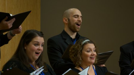 Choro in Schola singers (l-r) Amber Schroeder, Ben Espana, and Anne McKee Reed bring expressive faces as well as voices.