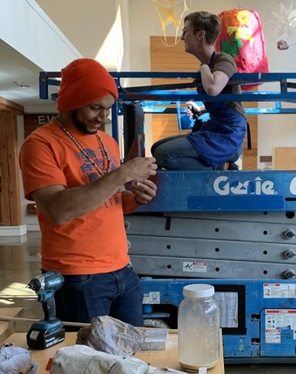 "Artist Michael Bernard Stevenson Jr. (left) and Carissa Burkett of the Chehalem Cultural Center work on the installation of ""Finn Builds a Galaxy."" Photo by: David Bates"
