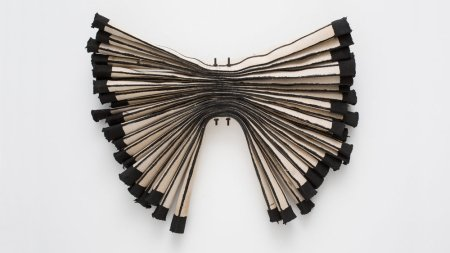 Sections of white cloth firehose with black ends, layered and gathered in a bow-shaped formation, mounted on gallery wall.