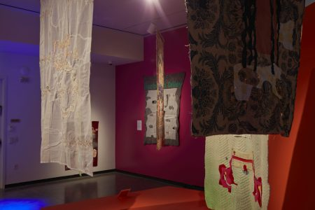 Gallery view with handmade scrap fabric banners hanging at various angles from ceiling, one wall is painted deep red-orange.