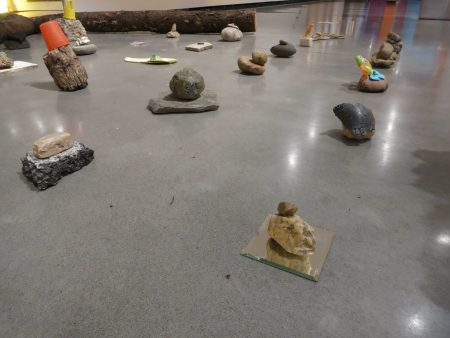 An assortment of various colorful objects including rocks and plastic toys and garbage arranged in a grid on gallery floor.