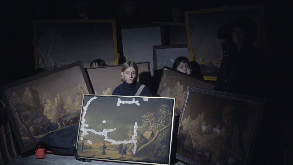 Still from video featuring several somber people in a darkened environment, each holding a large antique landscape painting, some paintings have tape over the canvas in places where they have been damaged