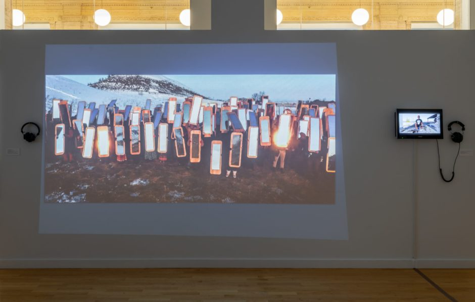 Gallery wall with video projection showing about twenty people standing in a group in a snowy rural landscape holding up reflective body-length shields in front of themselves, next to the projection is a small video screen and a pair of headphones hanging next to it.