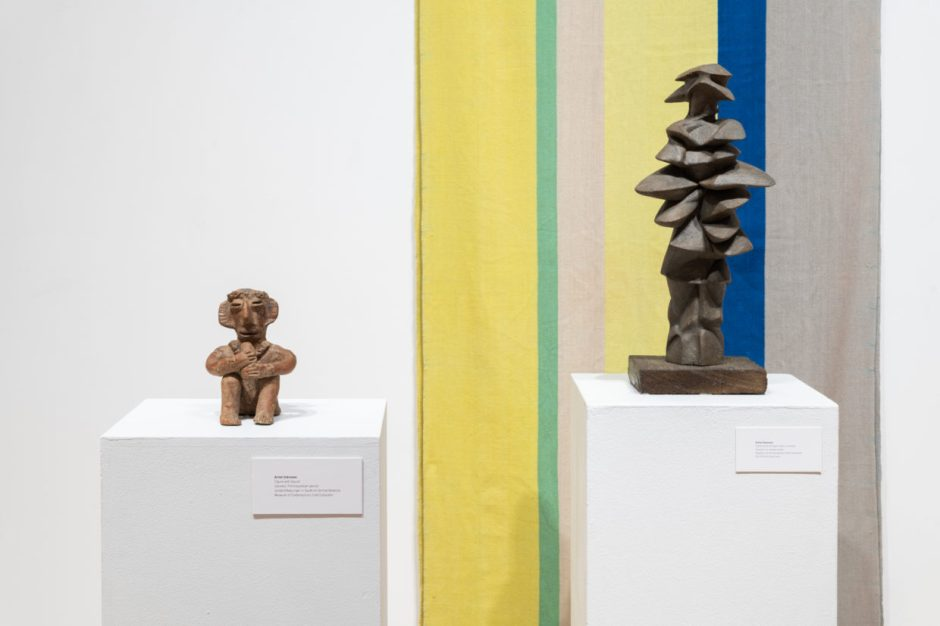 Two ceramic sculptures on pedestals in front of a woven tapestry in wide stripes of muted yellow, blue, gray, and green, One sculpture is a terracotta seated figurine with large ears that appears to be playing a flute, the other is an abstract stack of flat, pebble-like forms that vaguely resembles a human figure