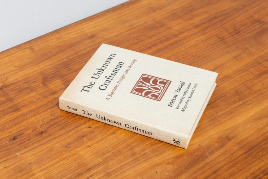 A vintage hardcover book with black lettering and a red insignia on off-white paper on a wooden bench
