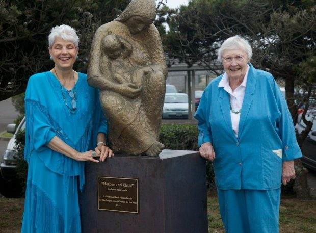 """Catherine Rickbone (left) joins sculptor Mary Lewis at her piece """"Mother and Child,"""" which was a gift to the Oregon Coast Council for the Arts in 2014. Photo courtesy: Oregon Coast Council for the Arts"""