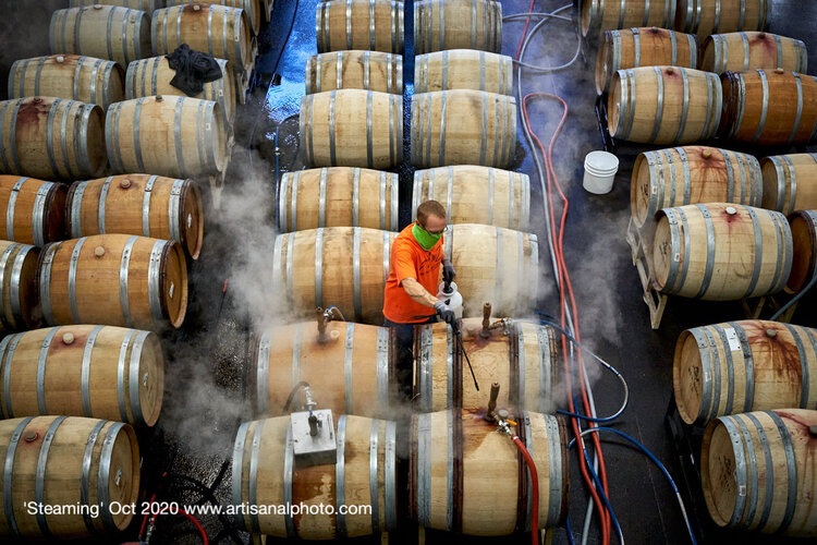 """""""Steaming"""" (October 2020) shows a worker preparing 60-gallon barrels to be filled with wine. """"I wanted to capture the scale of this operation,"""" Chitty writes, """"so placed Ryan in the center and had the rows of barrels as a continuum behind him. We don't know how far they stretch, or whether he's just started or is halfway through. Here is another example of a manual human task that accompanies winemaking at scale."""