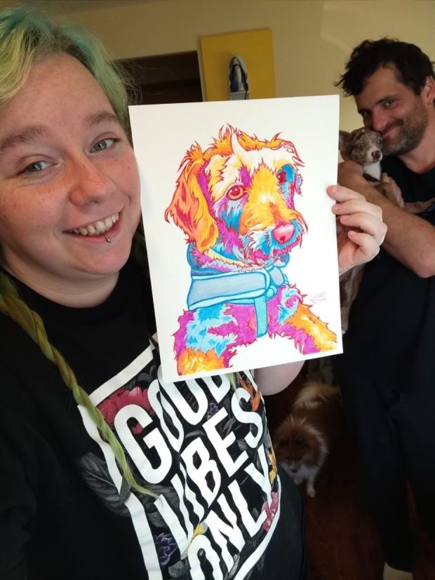 Ashley Andersen and her boyfriend, Jason Taylor (holding their dog, Shenzie) lost their house, cars, boat, and cat in the Echo Mountain Complex Fire. She is holding a commissioned gouache portrait created after the September fire.