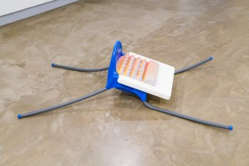 """An IKEA highchair is at the center of Colin Kippen's """"Feed & Nourish"""" (cement, IKEA high chair, flexible conduit, plastic pipe, acrylic paint; 18 by 36 by 65 inches, 2020)."""