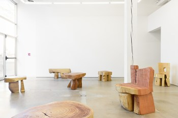 post and lintel structures out of roughly hewn wood shapes in a cement-floored and white-walled gallery