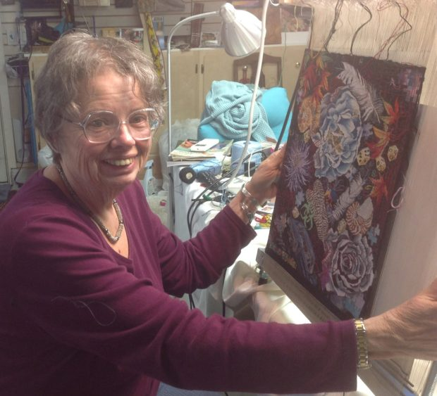 """Kathe Todd-Hooker works on a 14-by-14-inch tapestry she calls """"Nasty Ladies unite!!!! Do it now before it is too late!"""""""