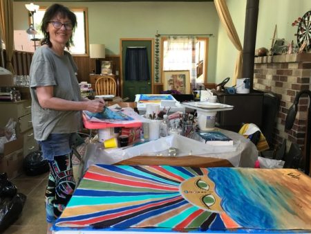 Amy Anderson, vice president of Alsea Bay Center for the Arts, prepares banners in her home studio for hanging in downtown Waldport. Photo by: Cheri Brubaker/YachatsNews.com