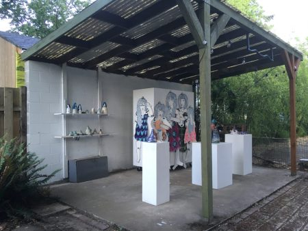 plinths with ceramics and a wall with figures with patterned clothing on it
