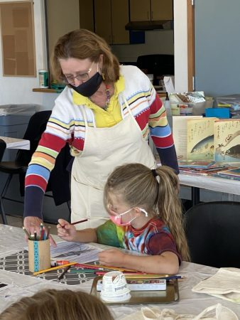 Volunteer Liz Olsen works with youngsters in the Newport Visual Arts camp earlier this summer. Arts Bus organizers hope the bus will bring creative opportunities to children who cannot make it to the Visual Arts Center for classes.
