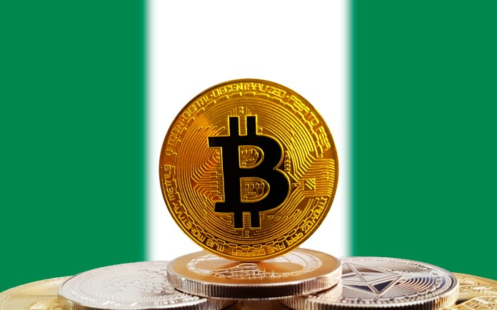 Bitcoin standing on top of other bitcoins with a Nigerian flag in the background