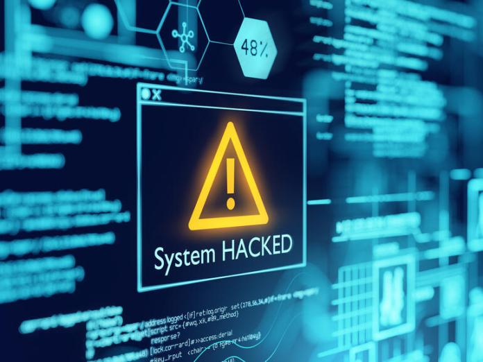 Picture of a computer screen with a box with a caution symbol with system hacked written underneath it, depicting Poly Network crypto hack