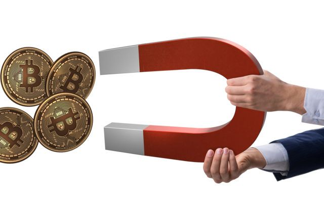 Picture of a hand attracting four gold bitcoin crypto coins with a giant red and white magnet