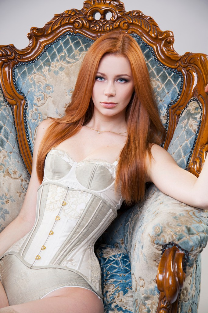 Model seated in armchair, wearing a gold and ivory silk Edwardian underbust training corset