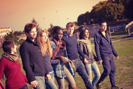Young adult student outdoors holding hands and walking