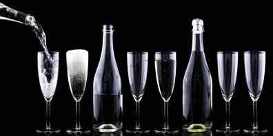 Sektflaschen und Sektgläser in einer Reihe