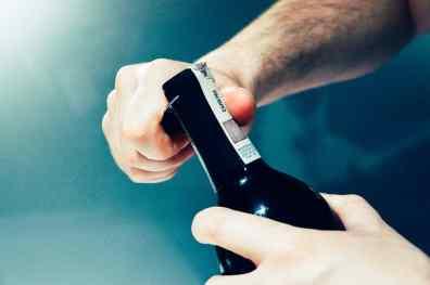 Die Hände eines Mannes, die eine Flasche Rotwein öffnen