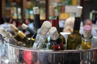 Ein Kühler voller offener, wieder mit Korken verschlossenen Weinflaschen