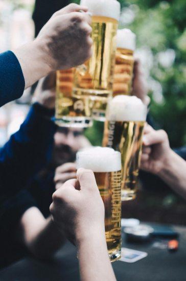 Sich mit Bier zu prostende Menschen
