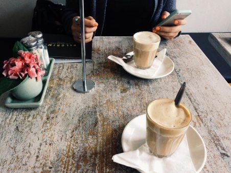 Ein Gast sitzt an einem Tisch im Café mit zwei Kaffee