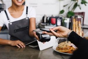 Ein Gast bezahlt in einer Gastronomie mit Apple Pay (kontaktloses Bezahlen via Smartphone)
