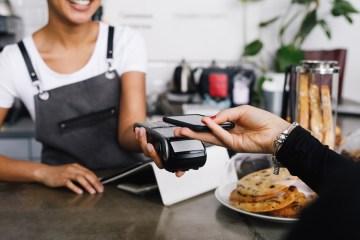 Ein Gat bezahlt in einer Gastronomie mit Apple Pay (kontaktloses Bezahlen via Smartphone)