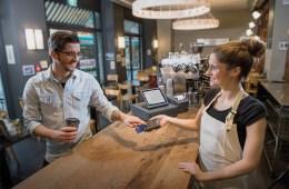Registrierkassenpflicht: Kellnerin kassiert an Tresen mit iPad-Kassensystem ab