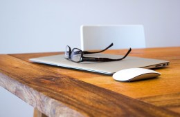 Ein Laptop mit Maus und Brille auf einem Holztisch
