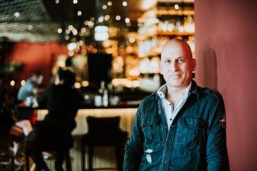 Frédéric Schuhmacher, der Experte für innovative Gastro-Trends, steht lächelnd vor einer Bar
