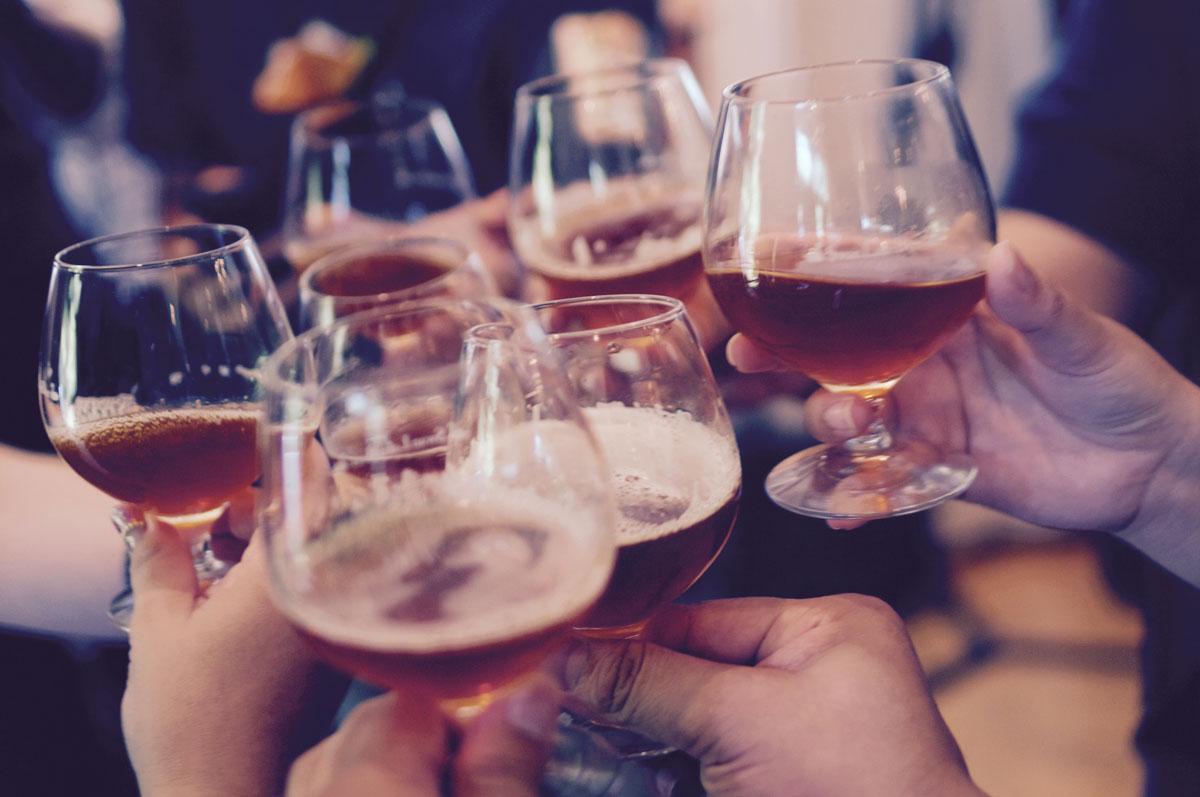 Biergläser von anstoßenden Kollegen auf der Firmenweihnachtsfeier