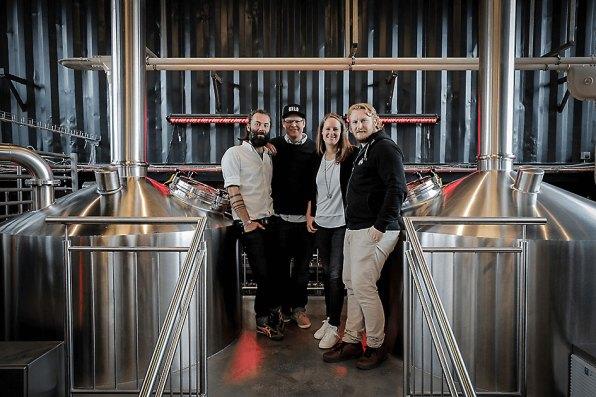 Die vier Gründer des BRLO BRWHOUSE in ihrer Brauerei zwischen den Braukesseln