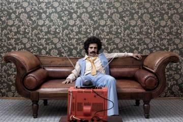 Ein Mann aus den 70igern sitzt auf einer Couch vorm Fernseher