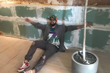 Der Gastro-Gründer Hussein sitzt vor seiner teilrenovierten Wand