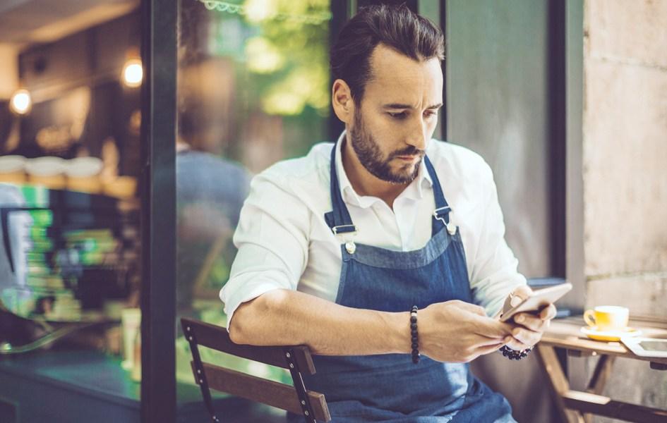 Ein Gastronom sitzt vor seiner Gastronomie und prüft Facebook local
